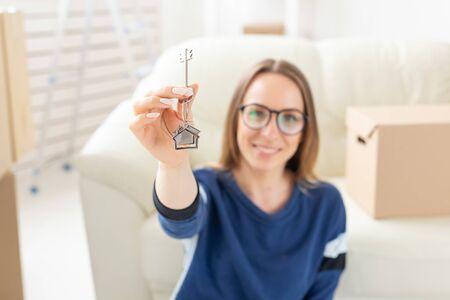 Umzugs-, Immobilien- und Wohnungskaufkonzept - Glücklicher alleinerziehender Wohnungsbesitzer oder Mieter, der Schlüssel zeigt und Sie anschaut