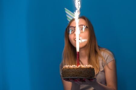 Cheerful young blurred girl student in glasses holding a congratulatory cake with a candle standing on a blue background. Birthday concept.
