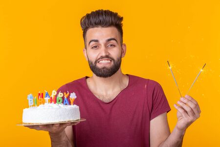 Positive young man holding a happy birthday cake and two burning bengal lights posing on a yellow background.
