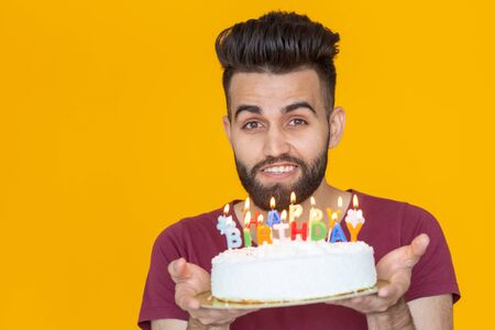 Close-up young handsome man blows off a candle from a burning cake posing for a yellow background. Holiday concept. Imagens