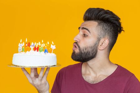 Side view of a handsome arab young bearded man blowing off candles with a congratulatory cake posing on a yellow background