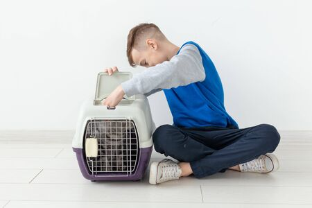 Laughing little positive boy holds a cage with a scottish fold cat next to him sitting on the floor in a new apartment. Pet protection concept. Stock Photo - 128613116