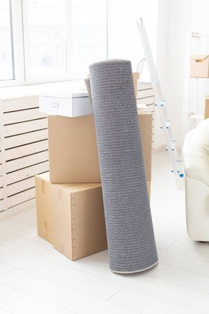 Cardboard boxes, sofa and carpet - moving to a new house Stockfoto - 128614815