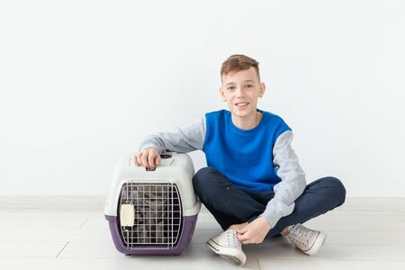 Laughing little positive boy holds a cage with a scottish fold cat next to him sitting on the floor in a new apartment. Pet protection concept. Stock Photo - 128613159