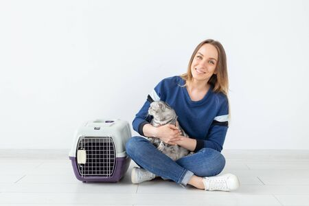 Charming positive young woman holds in her hands her beautiful gray fold scottish cat sitting on the floor in a new apartment. Pet concept. Stock Photo