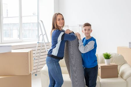 Relocation, housewarming and real estate concept - Smiling single mother and a charming son are holding a folded carpet in a new living room intending to spread it in a new apartment 版權商用圖片