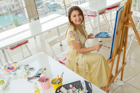 Art class and drawing concept - Woman artist working on painting in studio.