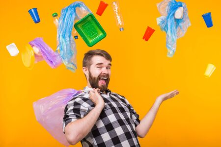 Problem of trash, plastic recycling, pollution and environmental concept - funny man holding garbage for recycling on yellow background.