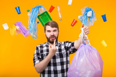 Plastic recycling problem, ecology and environmental disaster concept - Angry man holding garbage bag on yellow background
