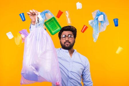 Problem of trash, plastic recycling, pollution and environmental concept - man carrying garbage bag on yellow background Imagens