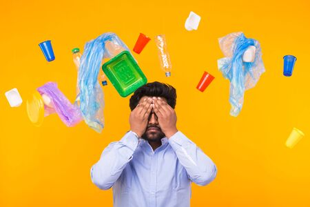 Plastic recycling problem, ecology and environmental disaster concept - Indian man closed his eyes with hands on yellow background. He is terrified by trash problems