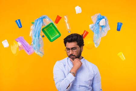 Problem of trash, plastic recycling, pollution and environmental concept - pensive indian man on yellow background with garbage.
