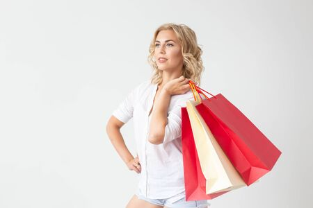 Charming young joyful blonde woman holds in her hands bags with a new clothing posing on a white background with copy space. Shopping concept.