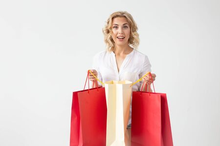 Positive young stylish blonde woman holding bags posing on a white background with copy space. Shopping concept in a mall. Stock Photo