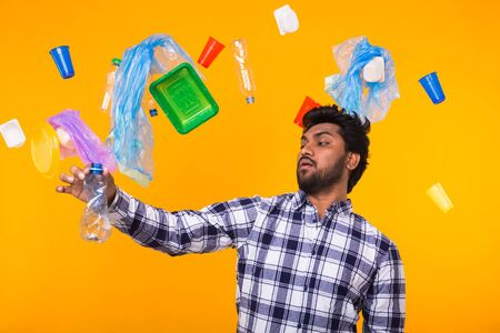 Environmental pollution, plastic recycling problem and waste disposal concept - surprised Indian man holding crumpled plastic bottle on yellow background.
