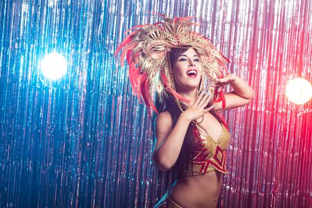 Cabaret, dancer and holidays concept - Cute young girl in bright colorful carnival costume on dark background