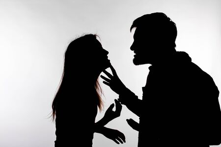 Relationship difficulties, conflict and abuse concept - man and woman face to face screaming shouting each other dispute silhouette isolated on white background. Stockfoto