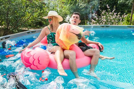 Problem of trash, plastic recycling, pollution and environmental concept - silly man and woman swim and have fun in a polluted pool. Bottles and plastic bags float near them Imagens