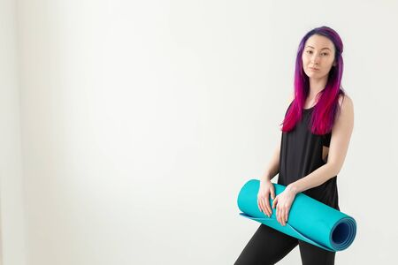 Young nice girl hipster with colored hair holding in hand a sports mat posing on a white background with copy space. Healthy lifestyle concept.