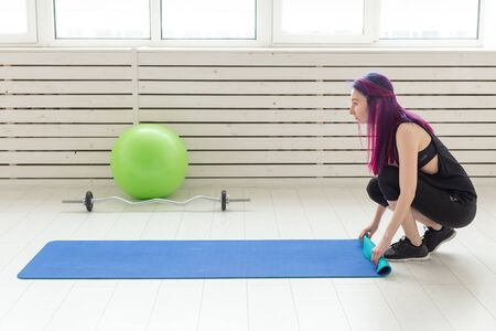 Slim young girl hipster with colored hair lay a gymnastic mat on the floor In the bright gym before the start of training. Concept of a slim healthy body and sports lifestyle.