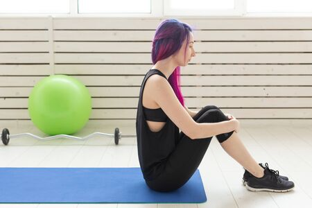 Young slim girl with colored hair makes an headstand on a sports blue mattress next to a barbell and green fitball. Concept of good physical fitness and regular training in the gym. Stock Photo