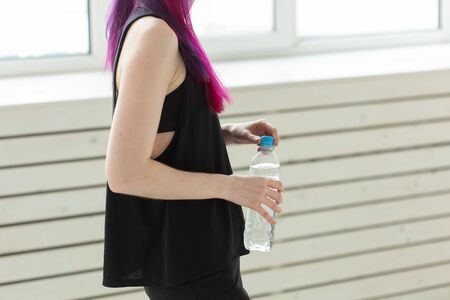 Close up of asian woman holding water after gym workout. Concept of replenishing water balance and a healthy lifestyle. Stock Photo