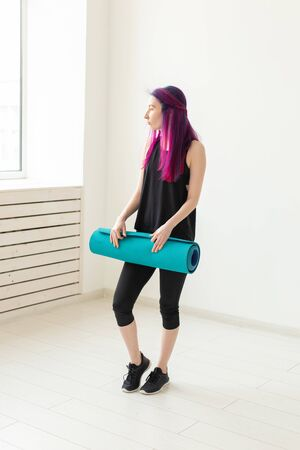 Slim young mixed race girl hipster with colored hair folds gymnastic mat after yoga in the gym Stock Photo