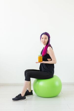 Cute young mixed race hipster girl with colored hair sitting on a green fitball and holding a banana protein smoothie in her hands on a white background. Healthy eating and exercise concept. Vertical shot