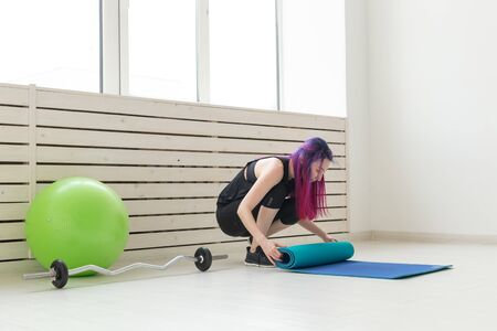 Young slim hipster girl with colored hair folds gymnastic sports mat and after class in the gym. Concept of yoga and pilates.