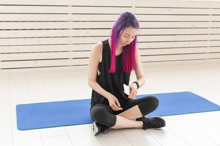 Young slim asian woman with purple hair looking a the pulse and burned calories using a smart watch and a smartphone while sitting on sports mats in a gym. Concept of an application for sports. Stock Photo