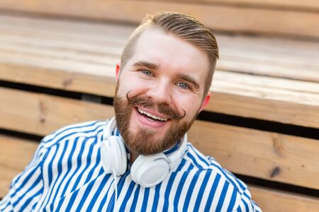 Portrait of a handsome young student guy with a mustache and a beard relaxing in a park with headphones on a warm summer day. Weekend getaway concept.