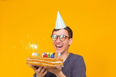 Crazy cheerful young man in glasses and paper congratulatory hats holding cakes happy birthday standing on a yellow background. Jubilee congratulations concept.