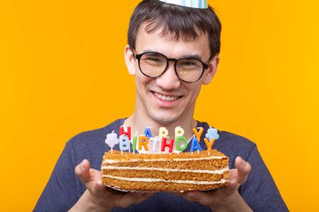 Portrait of a funny positive guy with a paper cap and glasses holding a congratulatory homemade cake in his hands on a yellow background. Concept and fun and celebration. Фото со стока