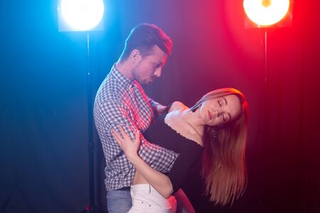 Social dance, bachata, salsa, kizomba, zouk, tango concept - Man hugs woman while dancing over lights