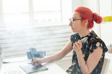 graphic designer concept - Female graphic designer working on computer while using graphic tablet at desk in the office and smoking a vape
