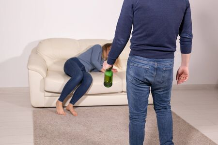 People, violence and abuse concept - Man drinking alcohol while wife is lying on sofa 版權商用圖片
