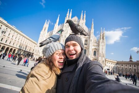 Couple taking self portrait with pigeon in Duomo square in Milan. Winter traveling, Italy and relationship concept