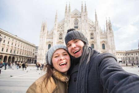 Couple taking self portrait in Duomo square in Milan. Winter traveling, Italy and relationship concept