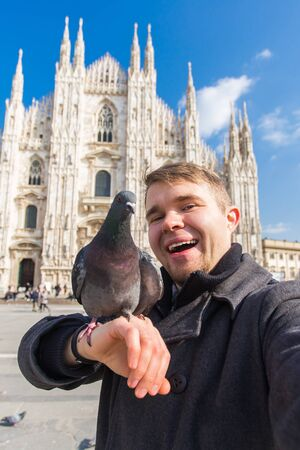 Travel, holidays and winter vacations concept - Happy man take selfie photo with funny pigeons in front of Duomo Milan Cathedral