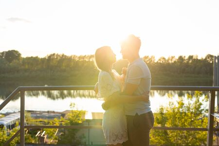 Man and woman hugging in sunset on nature. Couple in romantic embrace