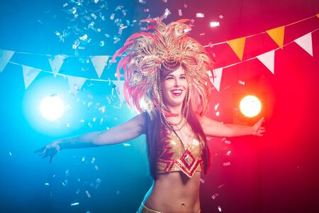 Carnival, dancer and holiday concept - Portrait of a sexy female in a colorful sumptuous carnival feather suit. Nightlife of female dancer