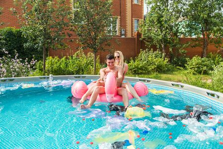 Problem of trash, plastic recycling, pollution and environmental concept - silly man and woman swim and have fun in a polluted pool. Bottles and plastic bags float near them
