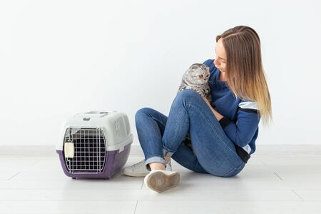 Charming positive young woman holds in her hands her beautiful gray fold scottish cat sitting on the floor in a new apartment. Pet concept. Standard-Bild