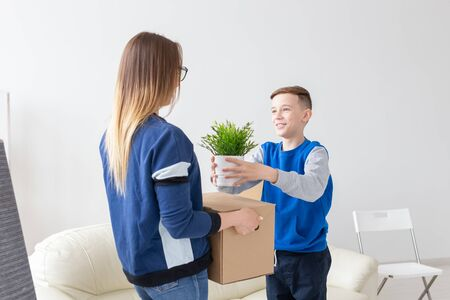 Young single mother and a playful little son are holding a box with things and a flower in a pot standing in the living room in a new apartment. Housewarming and new housing concept.