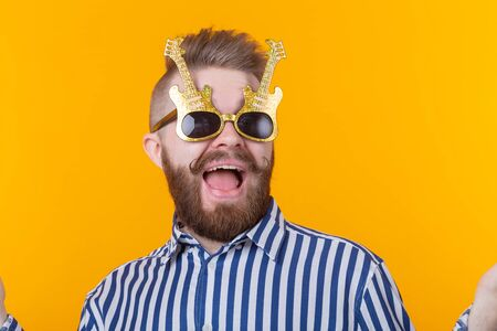 Positive young man with glasses in the form of guitars rejoices against a yellow background. The concept of celebration and parties. Stok Fotoğraf