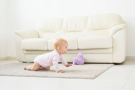 Childhood, children and babyhood concept - crawling funny baby girl indoors at home 스톡 콘텐츠 - 129191346
