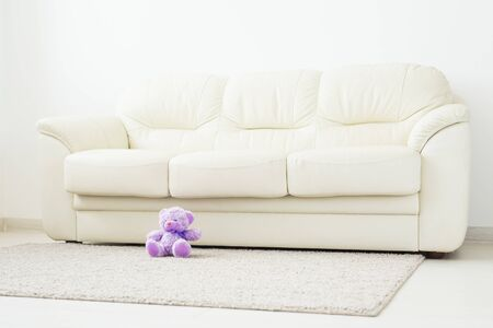 Childhood and babyhood concept - Teddy bear seated on beige carpet at bedroom