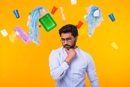 Environmental pollution, plastic recycling problem and ecology problem concept - pensive indian man on yellow background with garbage