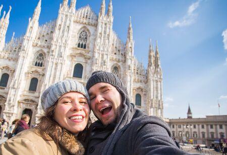 Grappig paar dat zelfportret neemt op het Duomo-plein in Milaan. Winterreizen, Italië en relatieconcept Stockfoto