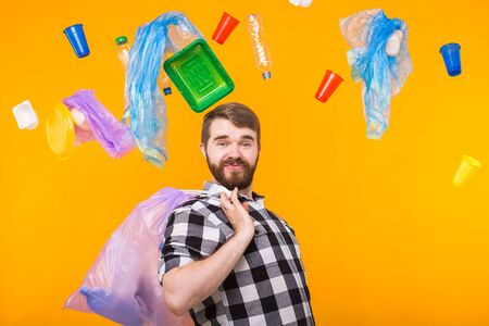 Environmental pollution, plastic recycling problem and ecology problem concept - proud funny man holding garbage for recycling on yellow background. 写真素材
